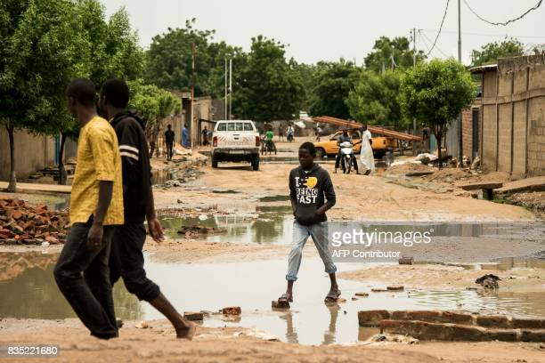 In this photograph taken on August 15 pedestrians walk through puddles in a street in the Chadian capital of N'Djamena after heavy rainfall / AFP...