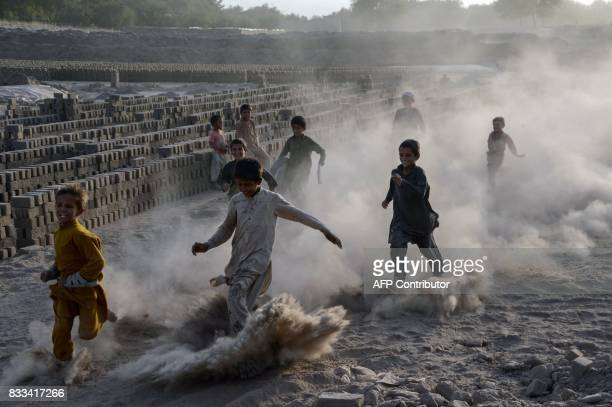 TOPSHOT In this photograph taken on August 16 Afghan children run as they play along a dusty road on the outskirts of Jalalabad / AFP PHOTO /...