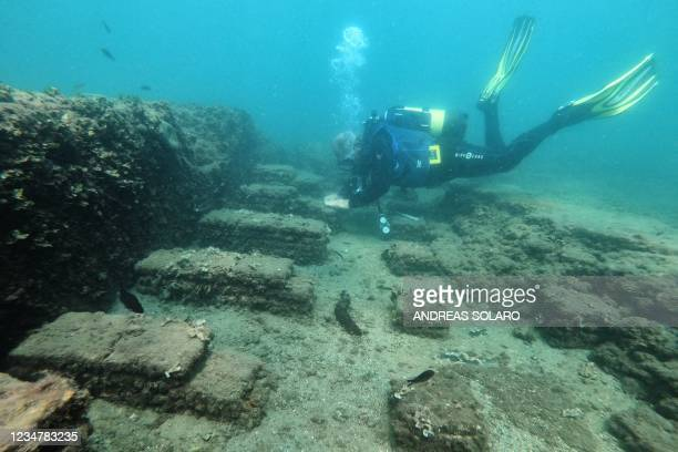 In this photograph taken on August 18, 2021 a dive guide shows tourists a archaeological find from the Roman era from Villa a Protiro, the submerged...