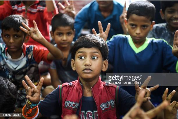 In this photograph taken on August 18 a child holds his breath as he practices breathing techniques with their teacher Baburao Ladsaheb during a...