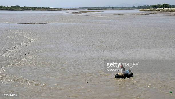 In this photograph taken on August 18 a Pakistani fisherman searches for fish as he sits on an inflated tube in the River Kabul at Hajji Zai village...