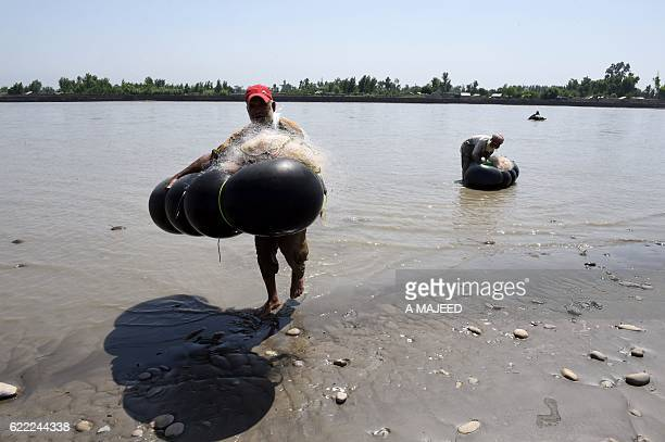 In this photograph taken on August 18 Pakistani fishermen carry their nets and tubes after catching fish from the River Kabul at Hajji Zai village in...