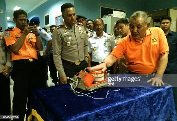 In this photograph taken on August 19 police and representatives of Indonesian transport safety official receive the recovered black box of Trigana...