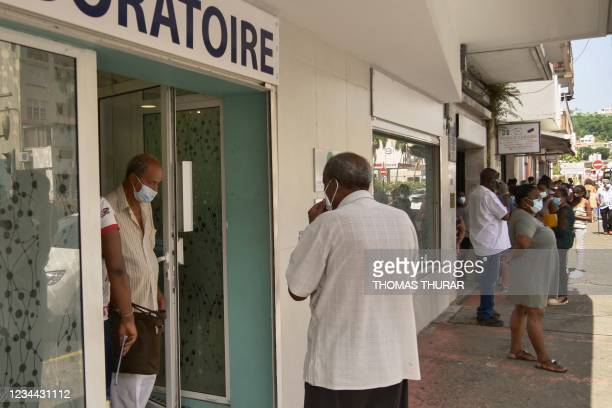 In this photograph taken on August 2, 2021 local residents queue up to take a Covid-19 test at a laboratory in Fort-de-France, in the French...
