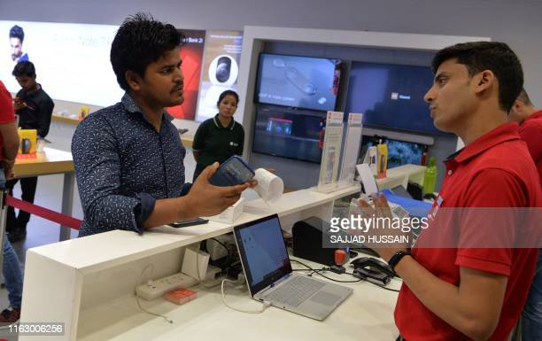 In this photograph taken on August 20 a salesman speaks with a customer after he purchased a new smartphone made by Xiaomi at a Mi store in Gurgaon.