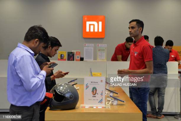 In this photograph taken on August 20 customers inspect smartphones made by Xiaomi at a Mi store in Gurgaon.