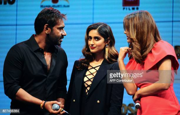 In this photograph taken on August 2017 Indian Bollywood actors Ajay Devgn and Ileana D'Cruz and Esha Gupta talk during the trailer launch of the...