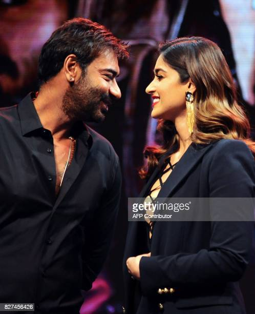 In this photograph taken on August 2017 Indian Bollywood actors Ajay Devgn and Ileana D'Cruz smile during the trailer launch of the upcoming Indian...
