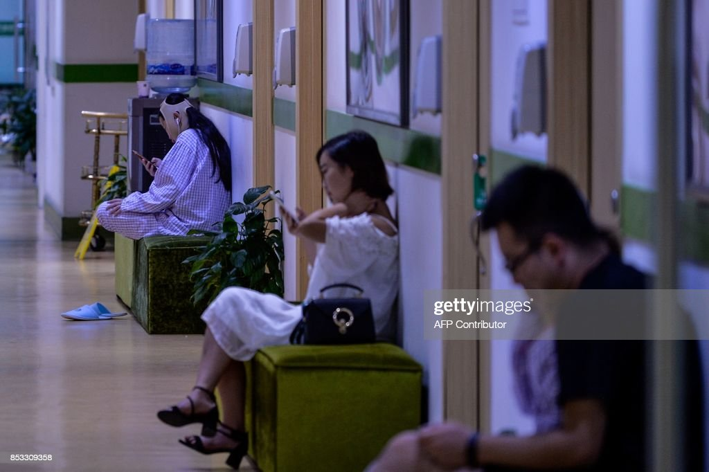 In this photograph taken on August 22, 2017, a young woman (L) with a bandaged face sits inside Huamei Medical Cosmetology Hospital in Shanghai. Plastic surgery is booming in China, fuelled by rising incomes, growing Western influences and the imperative of looking good on social media. / AFP PHOTO / CHANDAN KHANNA / To go with AFP story China-Lifestyle-Health-Social-Plastic, Feature by Peter Stebbings with Morgan Huang