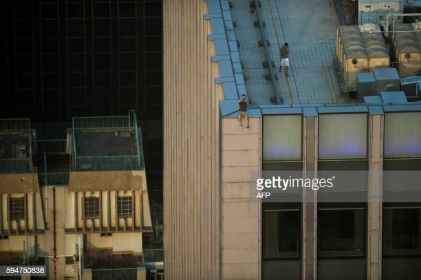 In this photograph taken on August 23 two men take a series of selfies as they sit on the ledge of a highrise building in an activity called...