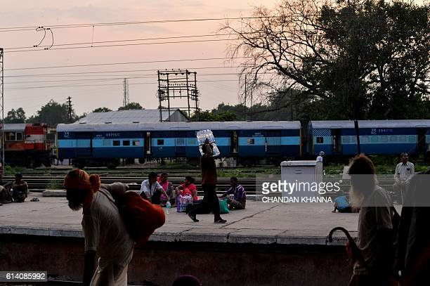 In this photograph taken on August 26 an employee of Indian Railways carries crate of water bottle across the railway platform in Mathura Passengers...