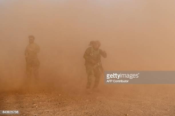 In this photograph taken on August 27 2017 a US special forces soldier and Afghan Commando take part in a combat training exercise at the Shorab...