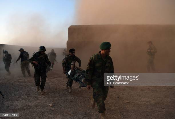 TOPSHOT In this photograph taken on August 27 2017 Afghan Commandos carry a colleague simulating an injury during a combat training exercise at...