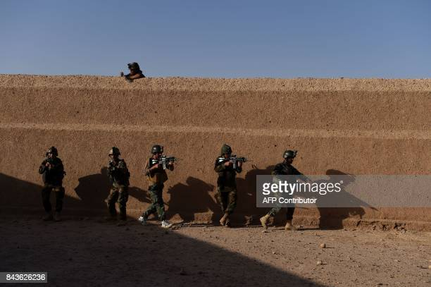 In this photograph taken on August 27, 2017 Afghan Commandos take positions during a combat training exercise at the Shorab Military Camp in Lashkar...