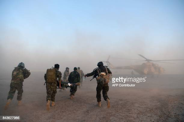In this photograph taken on August 27, 2017 Afghan Commandos transport a colleague feigning an injury on a stretcher as they participate in a combat...