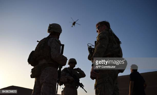 In this photograph taken on August 27, 2017 US Marines and Afghan Commandos stand together as an Afghan Air Force helicopter flies past during a...