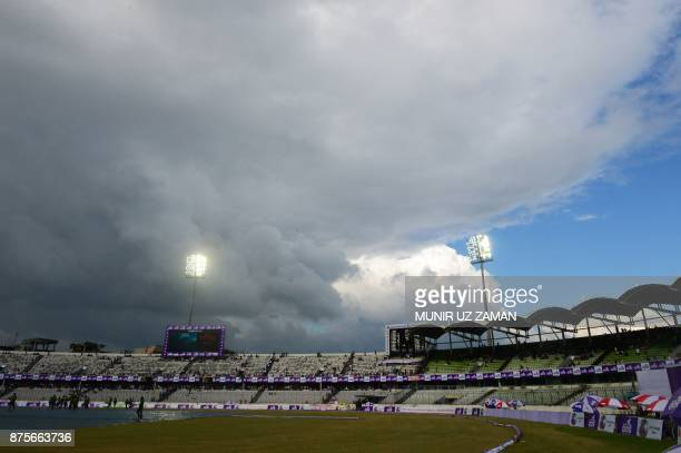 In this photograph taken on August 27 Bangladeshi ground staff cover the pitch as rain approaches during the first day of the first Test cricket...