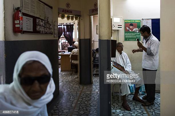 In this photograph taken on August 28 an Indian patient walks past an examination room as another undergoes an examination at the Dr Shroff Charity...
