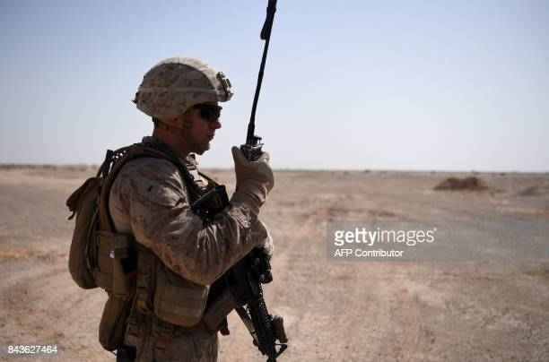 In this photograph taken on August 282017 a US Marines looks on as he talks on his radio as Afghan National Army soldiers clear the road during a...