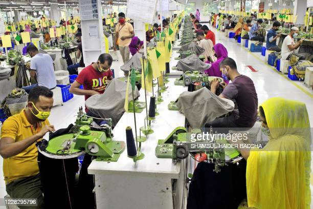 In this photograph taken on August 29 Bangladeshi labourers work in a garment factory in Gazipur. - Bangladesh's crucial textile industry saw a sharp...