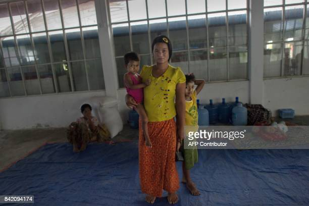 In this photograph taken on August 31 Oo Than Nu who lived along the Bangladesh border poses for a portrait with her children at an internally...