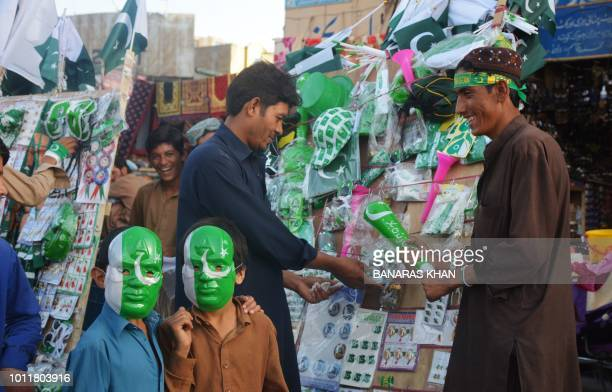 In this photograph taken on August 5 2018 Pakistani people shop at a roadside stall ahead of Independence Day celebrations in Quetta Pakistan will...