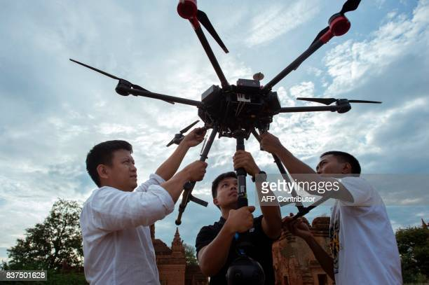 In this photograph taken on August 5 Nyi Lin Seck and other members of his team handle a drone carrying a 3604K video camera before releasing it in...