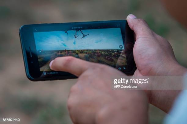 In this photograph taken on August 5 Nyi Lin Seck looks at footage he recoreded with his 3604K video camera while documenting the crumbling...