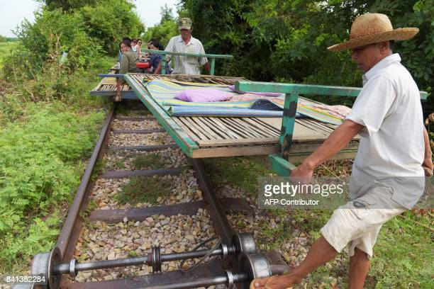 In this photograph taken on August 6 bamboo train operators take a bamboo platform off a small train wheel axle on one of Cambodia's abandoned...