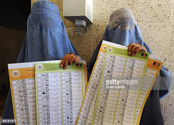 In this photograph taken on August 8 Afghan women holds up copies of ballot papers during an election awareness program at an eye hospital in Herat...