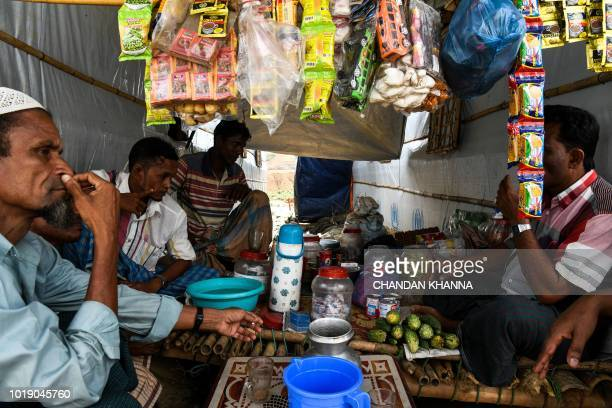 In this photograph taken on August 8 Rohingya refugee men sit at a makeshift shop in the Kutupalong camp in Cox's Bazar The Bangladeshi district of...