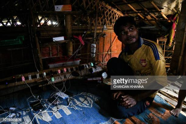 In this photograph taken on August 9 a Rohingya refugee works inside his mobile charging shop in the Kutupalong camp in Cox's Bazar The Bangladeshi...