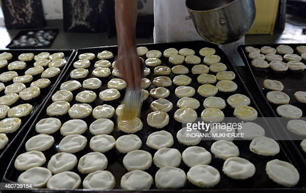 In this photograph taken on Dcember 19 2014 fourth generation Indian baker Emil Carvalho applies an egg coating onto traditional delicacies ahead of...