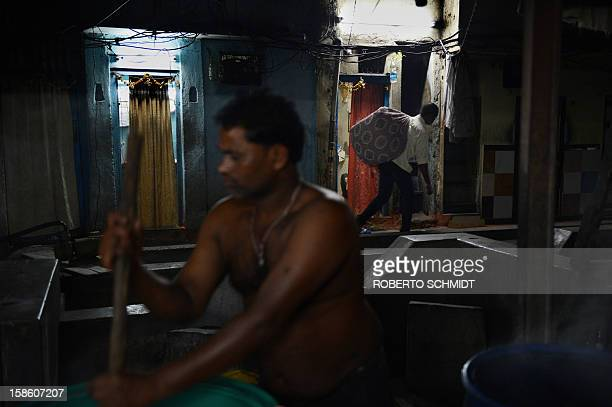 In this photograph taken on December 11 2012 a man carries a bunch of cleaned clothes on his back as another one stirs clothes in hot water at an...