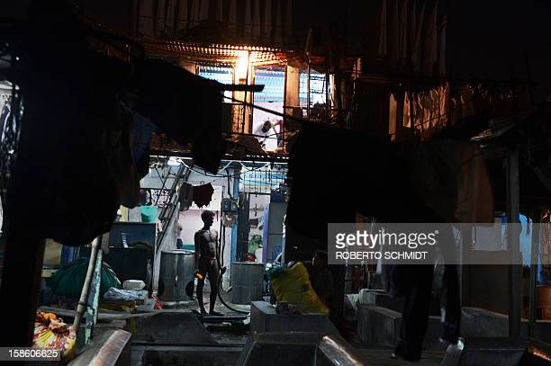 In this photograph taken on December 11 2012 a washer stands in front of a rooms where they live at an open air laundry facility known as the Dhobi...