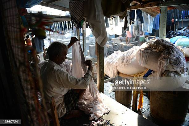 In this photograph taken on December 11 2012 a worker checks for thumbnail of a party table apron before they are washed at an open air laundry...