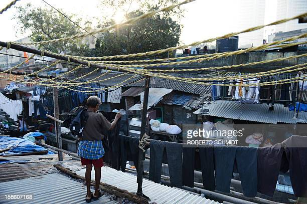 In this photograph taken on December 11 2012 a worker hangs clothes to dry on lines crowding tin roofs over an open air laundry facility known as the...