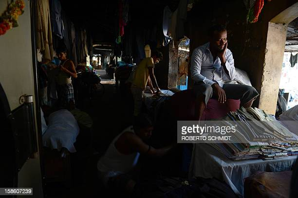 In this photograph taken on December 11 2012 a worker waits for a stack of shirts to be ironed before he delivers them back to their owner at an open...