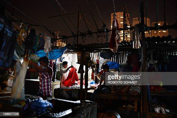 In this photograph taken on December 11 2012 workers wash and iron clothes at an open air laundry facility known as the Dhobi Ghat in Mumbai near...