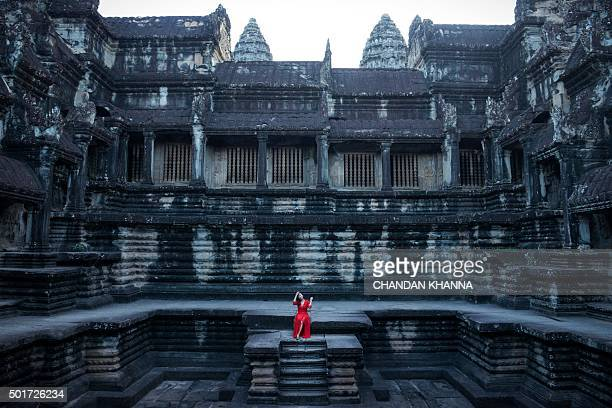 TOPSHOT In this photograph taken on December 12 a tourist poses for a photograph as she sits near a stepwell inside the Angkor Wat Temple in Siem...