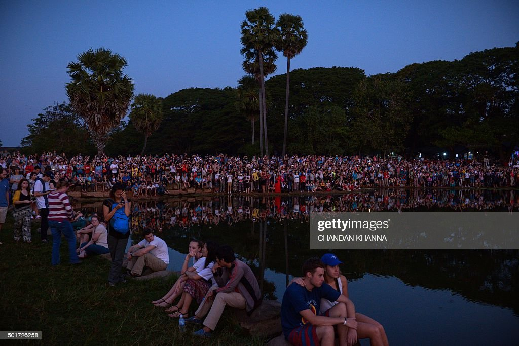 In this photograph taken on December 12, 2015, hundreds of tourists wait by the pond to see and photograph the sunrise behind the Angkor Wat Temple in Siem Reap. AFP PHOTO / CHANDAN KHANNA / AFP / Chandan Khanna