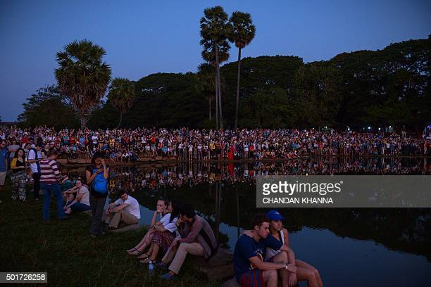 In this photograph taken on December 12 hundreds of tourists wait by the pond to see and photograph the sunrise behind the Angkor Wat Temple in Siem...