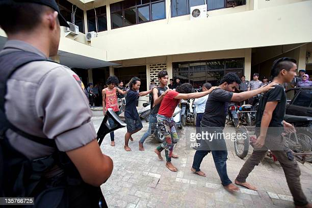 In this photograph taken on December 13 2011 police escort a group of arrested Indonesian punks in Bandah Aceh police station in Aceh province Sharia...