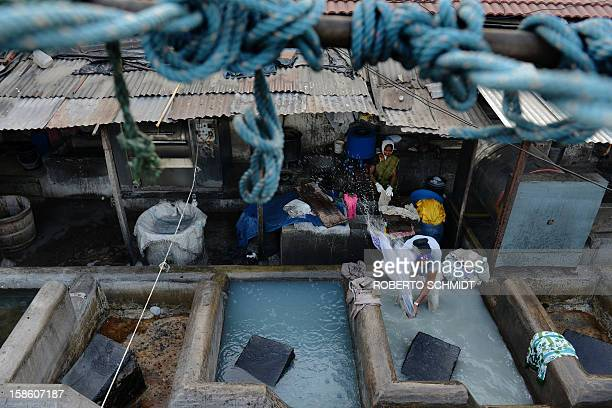 In this photograph taken on December 13 2012 a man and a woman wash clothes at an open air laundry facility known as the Dhobi Ghat in Mumbai This...