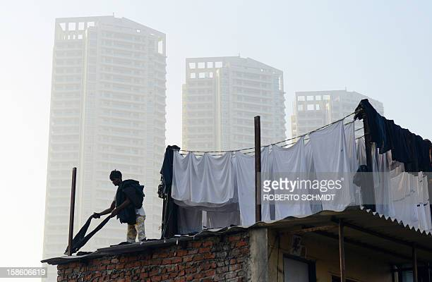 In this photograph taken on December 13 2012 a man lays pants to dry on a tin roof at an open air laundry facility known as the Dhobi Ghat near...