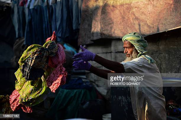 In this photograph taken on December 13 2012 a washer throws clothes to be washed into his washing pen at an open air laundry facility known as the...