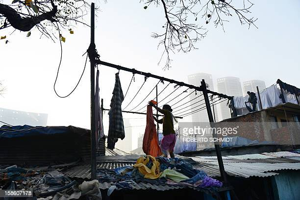 In this photograph taken on December 13 2012 a woman hangs clean clothes to dry at an open air laundry facility known as the Dhobi Ghat near luxury...