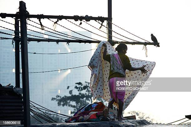 In this photograph taken on December 13 2012 a woman puts out a blanket up to dry on a tin roof at an open air laundry facility known as the Dhobi...