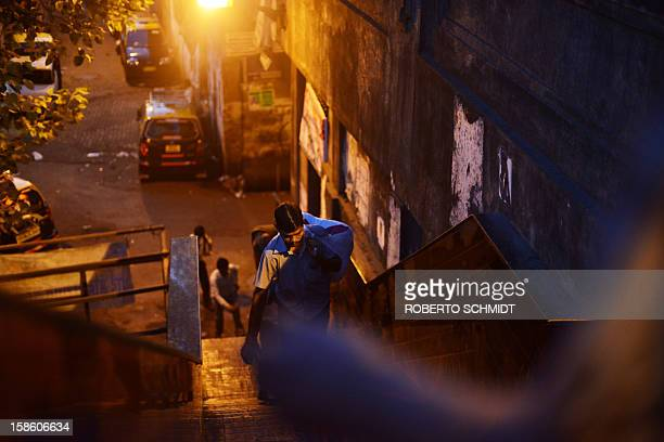 In this photograph taken on December 13 2012 a worker carries a bag with clean clothes for delivery as he leaves an open air laundry facility known...