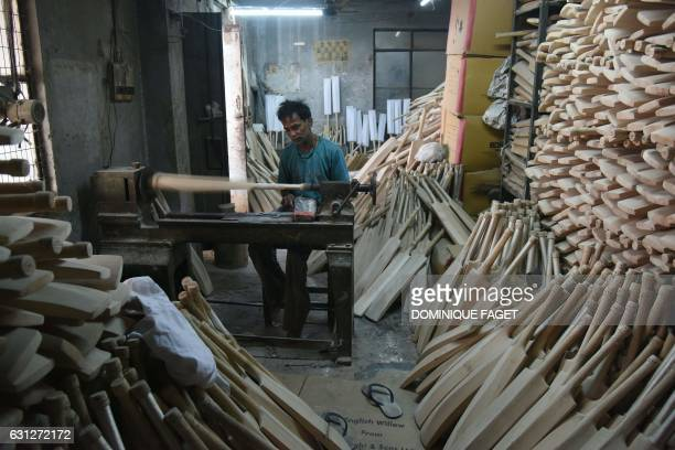 TOPSHOT In this photograph taken on December 14 an Indian craftsman works on unfinished cricket bats in a factory in Meerut some 70kms northeast of...